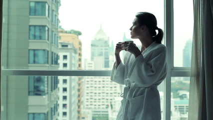 Silhouette of woman drinking coffee by the window with cityscape
