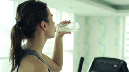 Tired woman drinking water after workout in the gym