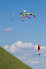 Paraglider flying against the czech central mountains