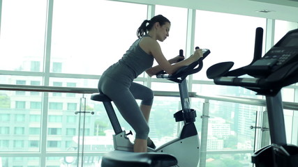Young woman riding at stationary bike in the gym