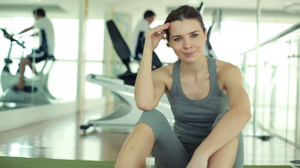 Portrait of young fit happy woman relaxing in the gym