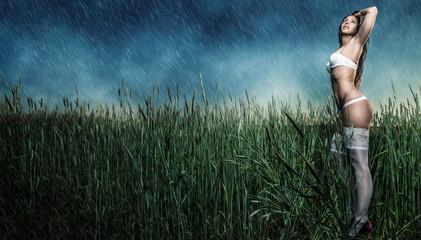Schöne Frau in weißen Dessous im Regen