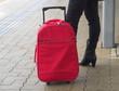 Frau verreist mit rotem Reisekoffer