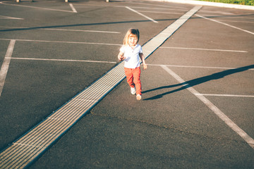 Little girl running away on the road