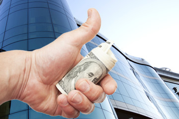 Hand with notes of dollars against office building