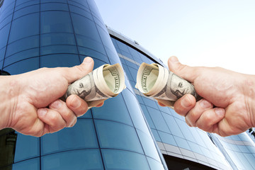 hands with notes of dollars against office building