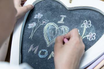 Boy writing I love mom on a heart shaped blackboard