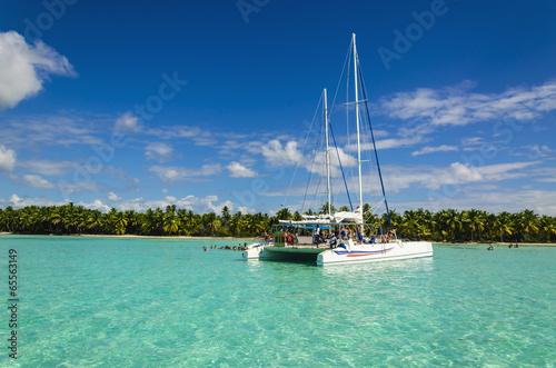 White catamaran on azure water against blue sky - 65563149
