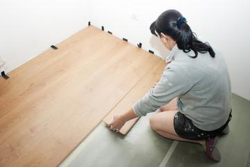 beautiful woman puts laminate flooring