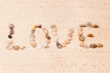 mot love écrit avec des galets sur le sable