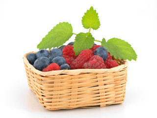 berries in braided basket on white background
