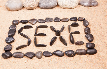 mot sexe écrit avec des galets sur le sable