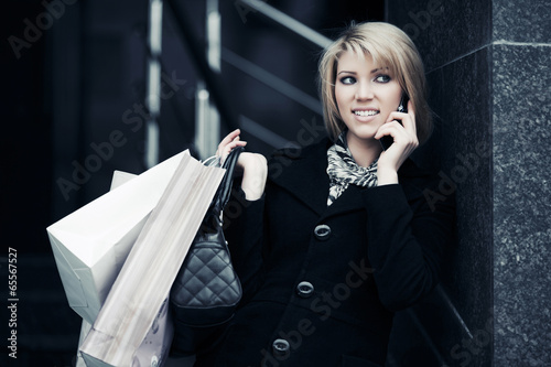 Blond woman with shopping bags calling on the phone