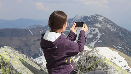 Woman uses a smartphone to video a beautiful view