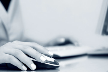 Female hands using computer mouse and keyboard
