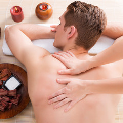 andsome man relaxed and enjoying back massage.