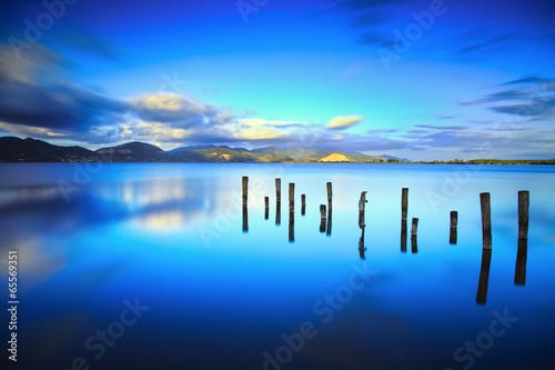 Drewniany molo lub molo zostaje na błękitnym jeziornym zmierzchu i nieba refle