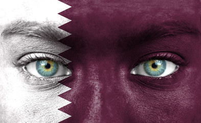 Human face painted with flag of Qatar