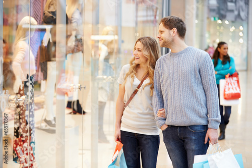 Happy Couple Carrying Bags In Shopping Mall