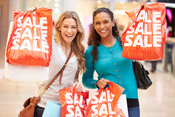 Two Excited Female Shoppers With Sale Bags In Mall