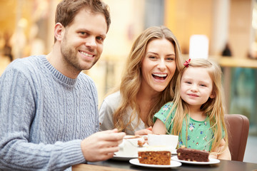 Family Enjoying Snack In Café Together