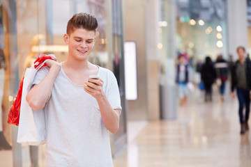 Man In Shopping Mall Using Mobile Phone