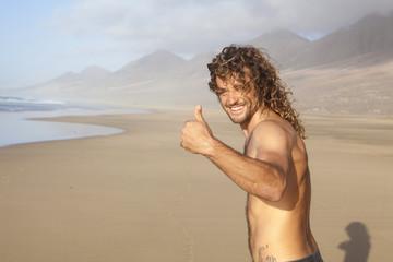young handome man on a desert beach