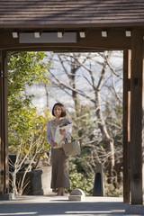山門に立ち花を持つ女性
