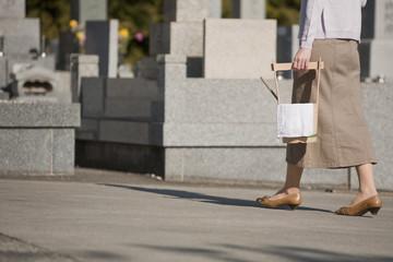 水桶を持ち墓地を歩く女性