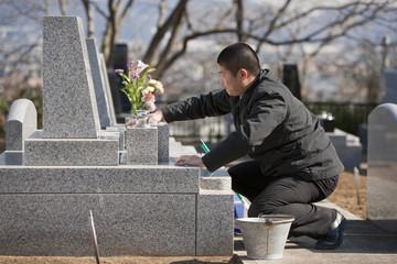 代行で墓の掃除をする男性
