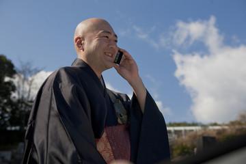 スマートフォンを使用する僧侶