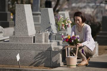 お墓に花を供える女性