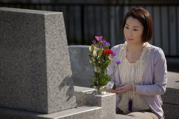 お墓に線香をあげる女性