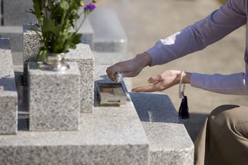 お墓に線香をあげる女性の手