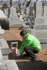 お墓参りの代行で手を合わせる男性