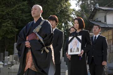僧侶の後ろを歩く遺影を持つ女性と遺族