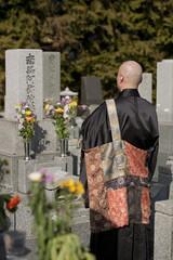 お墓の前で手を合わせる僧侶の後姿