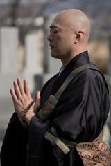 お墓の前で手を合わせる僧侶