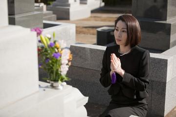 お墓の前で手を合わせる喪服姿の女性