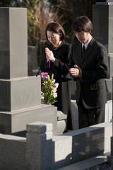 お墓の前で手を合わせる喪服姿の夫婦