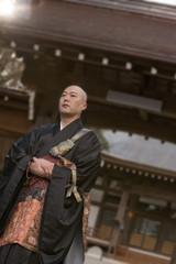山門の前に立つ僧侶