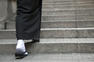 階段を登る喪服姿の女性の足元