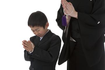 数珠を持って合掌する喪服姿の母と息子