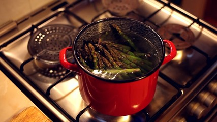 A bunch of asparagus boiling in a red steel bowl full of water