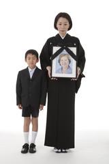 遺影を持って立つ喪服姿の母親と息子 正面