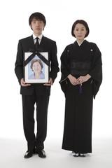遺影を持って立つ喪服姿の夫婦 正面