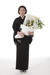 花を持って立つ喪服姿の女性 正面