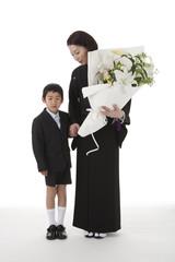 花を持って立つ喪服姿の母親と息子 正面