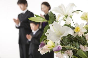 喪服姿で合掌する家族と祭壇の花