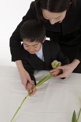 花を手向ける喪服姿の母親と息子